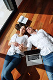 Entspannte junge Paare, die zu Hause an Laptop-Computer arbeiten Lizenzfreies Stockfoto