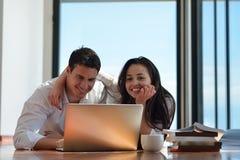 Entspannte junge Paare, die zu Hause an Laptop-Computer arbeiten Stockfotos