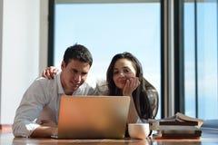 Entspannte junge Paare, die zu Hause an Laptop-Computer arbeiten Lizenzfreie Stockbilder