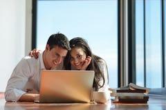 Entspannte junge Paare, die zu Hause an Laptop-Computer arbeiten Stockfoto