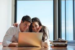 Entspannte junge Paare, die zu Hause an Laptop-Computer arbeiten Lizenzfreies Stockbild