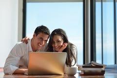 Entspannte junge Paare, die zu Hause an Laptop-Computer arbeiten Lizenzfreie Stockfotos