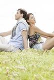 Entspannte junge Paare, die zurück zu Rückseite im Park sitzen lizenzfreie stockbilder