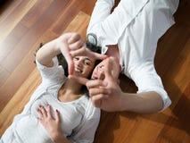 Entspannte junge Paare zu Hause lizenzfreie stockfotos