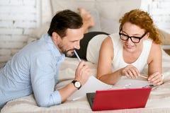 Entspannte Mitte gealterte Paare unter Verwendung des Laptops zu Hause Lizenzfreie Stockfotos