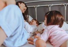 Entspannte Mutter und Söhne, die über dem Bett spielen Lizenzfreies Stockbild