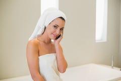 Entspannte natürliche braune behaarte Frau, die einen Telefonanruf macht Lizenzfreies Stockfoto