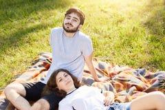 Entspannte Paare, die auf der Verpackung draußen hat das Picknick zusammen genießt gutes Wetter liegen Nettes junges weibliches L lizenzfreies stockfoto