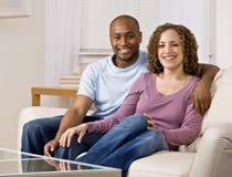 Entspannte Paare, die auf Sofa im Wohnzimmer sitzen Stockbild