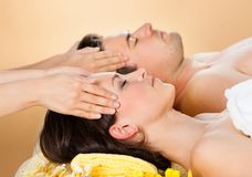 Entspannte Paare, die Kopfmassage am Badekurort empfangen Stockfotos