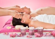 Entspannte Paare, die Kopfmassage am Badekurort empfangen Lizenzfreies Stockfoto