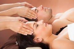 Entspannte Paare, die Kopfmassage am Badekurort empfangen Lizenzfreie Stockfotos