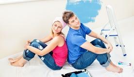 Entspannte Paare, die zurück zu Rückseite nachdem dem Malen sitzen Stockfotos