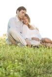 Entspannte Paare mit Augen schlossen das Sitzen auf Gras im Park lizenzfreie stockfotos