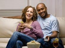 Entspannte Paare mit Popcorn und Fernsteuerungs Stockbild