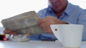 Entspannte Person in der Büro-Getränk-Kaffee-Rauch-Zigarette und in gelesener Tageszeitung stock video
