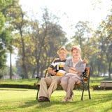Entspannte reife Paare, die einen sonnigen Tag im Park genießen Stockfotos