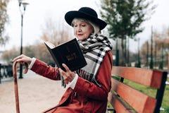 Entspannte reife weibliche Ausgabenfreizeit mit Buch lizenzfreie stockfotos