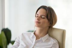 Entspannte ruhige aufmerksame Frau, die auf bequemem Bürostuhl stillsteht lizenzfreie stockfotos