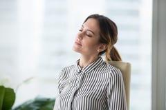 Entspannte ruhige Geschäftsfrau, die im ergonomischen Stuhl faulenzt bei der Arbeit stillsteht stockfoto
