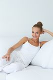 Entspannte schöne Frau, die auf Couch sitzt Lizenzfreie Stockbilder