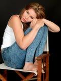 Entspannte schöne junge Frau, die in einem Stuhl sitzt Stockfoto