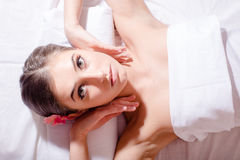 Entspannte Schönheit, die zurück auf ihrem liegt und Kamera während des Massagebehandlungs-Nahaufnahmeporträts betrachtet Lizenzfreies Stockfoto