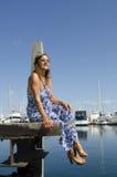 Entspannte und glückliche Frau, die am Jachthafen sitzt Lizenzfreie Stockfotos