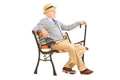 Entspannter älterer Mann, der auf einer Holzbank und einem Denken sitzt Stockbilder
