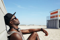 Entspannter afrikanischer Mann, der zu einer Wand am Strand sich lehnt Stockbild