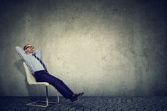 Entspannter Angestellter, der auf Stuhl sitzt lizenzfreies stockbild