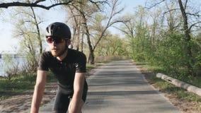 Entspannter athletischer geeigneter Radfahrer, der Fahrrad im Park fährt Front folgen Schuss Bärtiger Radfahrer, der einfache Fah stock footage