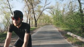 Entspannter athletischer geeigneter Radfahrer, der Fahrrad im Park f?hrt Front folgen Schuss B?rtiger Radfahrer, der einfache Fah stock video