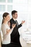 Entspannter aufmerksamer Geschäftsmann und Geschäftsfrau, die bei der Arbeit meditiert lizenzfreie stockfotos