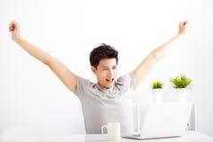 Entspannter aufpassender Laptop des jungen Mannes Lizenzfreie Stockfotos
