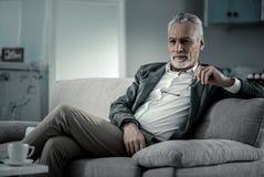 Entspannter bärtiger Mann, der auf Couch sitzt stockbild