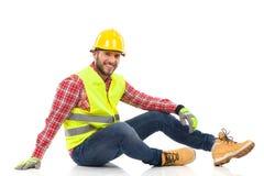 Entspannter Bauarbeiter, der auf einem Boden sitzt Lizenzfreie Stockfotos
