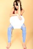 Entspannter gebohrter Fed Up Young Woman Sitting auf einem Stuhl stockfotografie