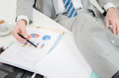 Entspannter Geschäftsmann, der Finanzdiagramme überprüft Lizenzfreie Stockbilder