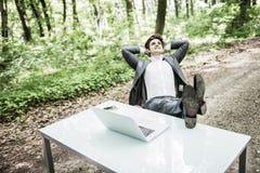 Entspannter Geschäftsmann in der Klage mit Köpfen Unkosten und Beine auf Schreibtisch nach erfolgreicher Arbeit im grünen Park Fr lizenzfreie stockfotos