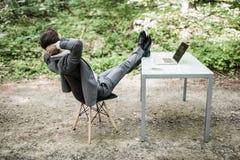Entspannter Geschäftsmann in der Klage mit Köpfen Unkosten und Beine auf Schreibtisch nach erfolgreicher Arbeit im grünen Park Fr lizenzfreies stockfoto