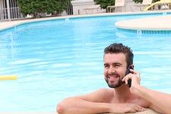 Entspannter Geschäftsmann unter Verwendung des Telefons durch Swimmingpool Stockfoto