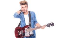 Entspannter Gitarrist mit der Hand hinter seinem Hals Stockbilder