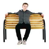 Entspannter Junge, der auf Bank sitzt Lizenzfreie Stockfotos