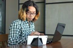 Entspannter junger asiatischer Hippie-Mann, der gegen Laptop und Tablette in seinem Büro arbeitet Stockfoto