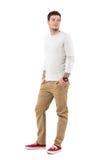Entspannter junger Mann in den beige Hosen und lächelndes zurück schauen des grauen Hemdes über Schulter Stockfotografie