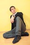 Entspannter junger Mann, der auf dem Fußboden sitzt stockfotos