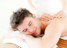 Entspannter junger Mann, der eine rückseitige Massage empfängt Stockfoto