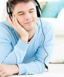 Entspannter junger Mann hören Musik mit Kopfhörern stockfotografie