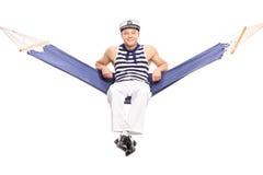 Entspannter junger Seemann, der auf einer Hängematte sitzt Stockfoto